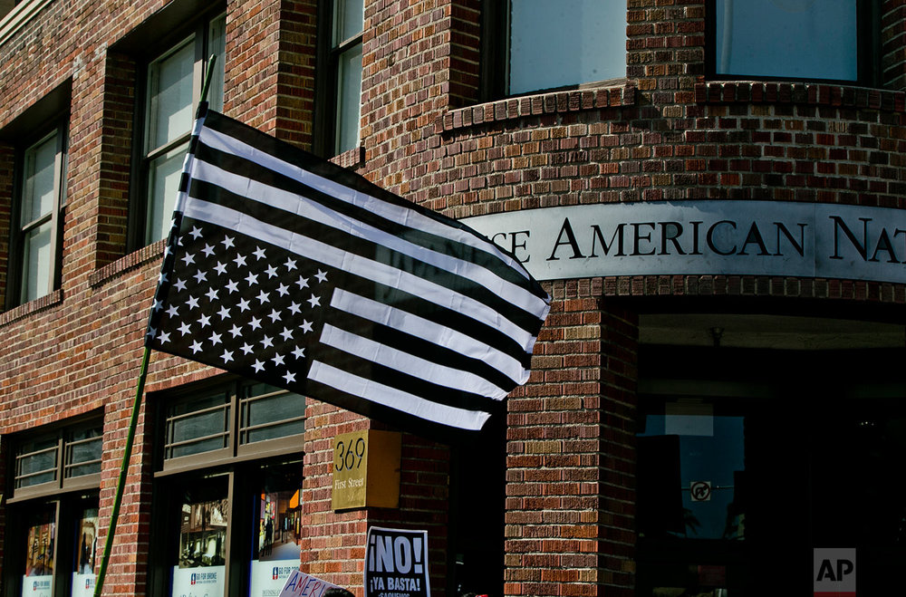 Protesters carry an upside down U.S. flag outside the Japanese American Museum in downtown Los Angeles on Sunday, Aug. 13, 2017 Protesters decrying hatred and racism converged around the country Sunday, the day after a white supremacist rally that spiraled into violence in Charlottesville, Va. (AP Photo/Damian Dovarganes)
