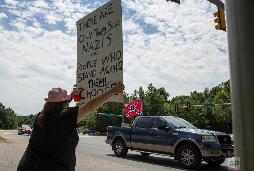 Kim Wyman of Spotsylvania, Va.,  joined more than 60 demonstrators at the intersection of the Blue and Gray Parkway and William Street in Fredericksburg, Va., Sunday, Aug. 13, 2017, to protest against hate and racism in the wake of violence in Charlottesville. (Mike Morones/The Free Lance-Star via AP)
