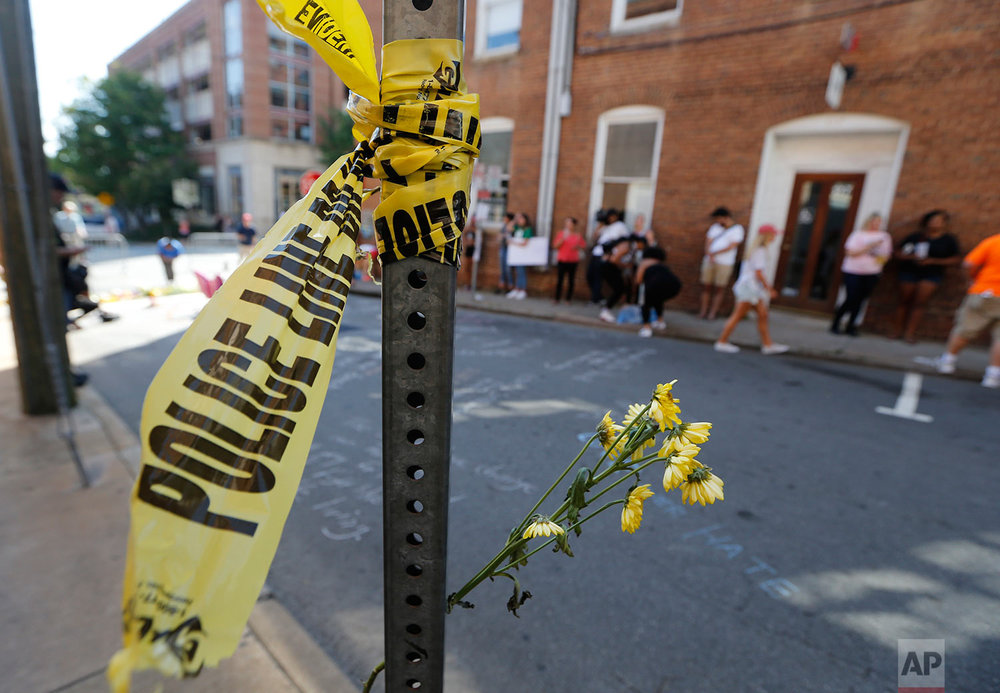 On Sunday, Aug. 13, 2017, police tape and flowers mark the site where a car plowed into a crowd of people protesting a white nationalist rally on Saturday in Charlottesville, Va. (AP Photo/Steve Helber)