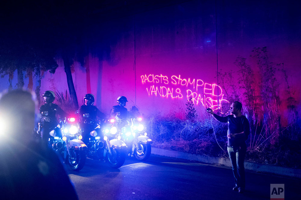 Graffiti spray-painted by a protester lines a wall as police officers clear demonstrators from a freeway off-ramp in Oakland, Calif., Saturday, Aug. 12, 2017. (AP Photo/Noah Berger)