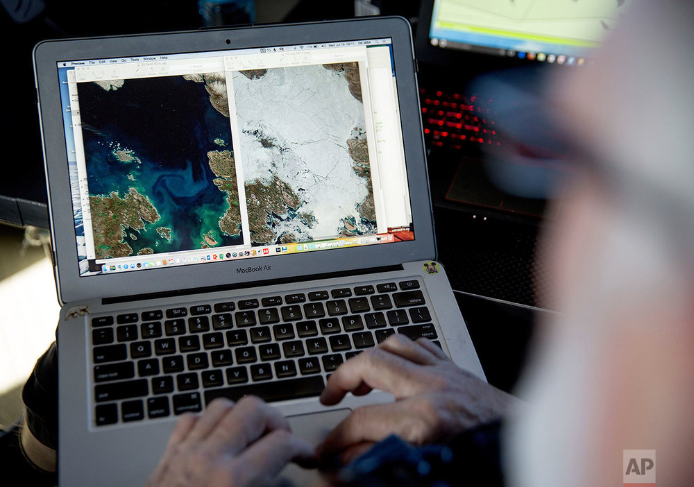 """Canadian ice navigator, David """"Duke"""" Snider compares satellite images of ice coverage from September 2016, left, to one from in July 2017 for the same area where the Finnish icebreaker MSV Nordica will be traversing the Northwest Passage through the Canadian Arctic Archipelago, Wednesday, July 19, 2017. More recent data show that not only is the Arctic sea ice coverage area shrinking, but the ice that's left is getting thinner too. Snider said he has seen the ice cover reduced in both concentration and thickness. (AP Photo/David Goldman)"""