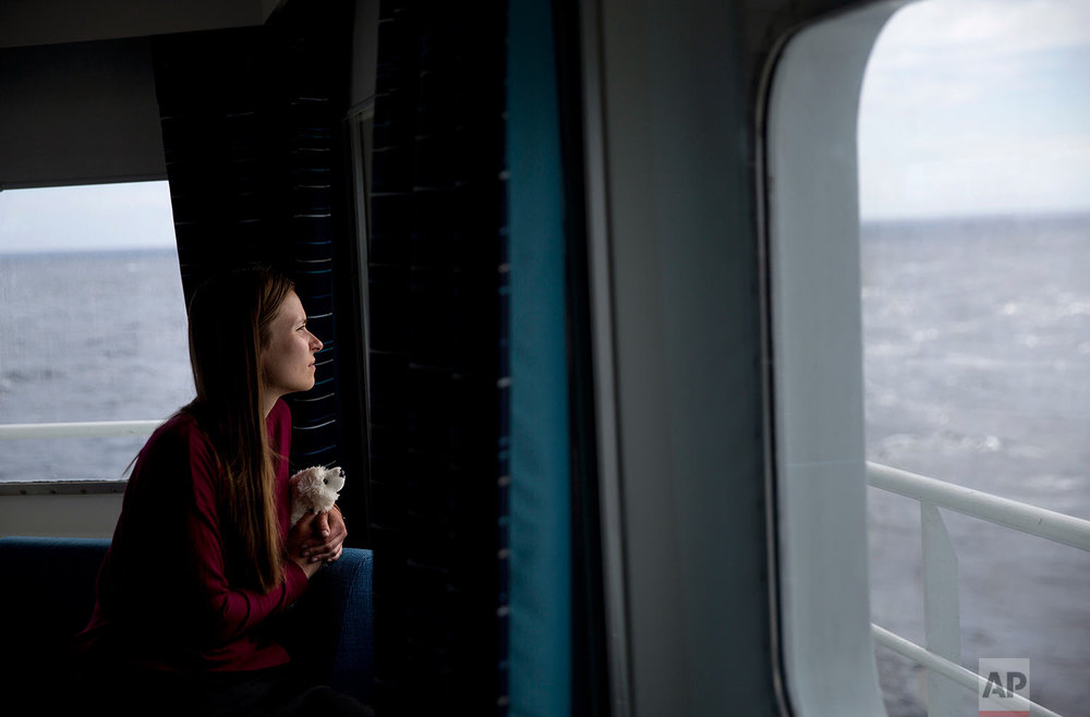 Researcher Daria Gritsenko holds her stuffed polar bear, Umka, while looking out from the Finnish icebreaker MSV Nordica as it sails the North Pacific Ocean to traverse the Northwest Passage through the Canadian Arctic Archipelago Monday, July 10, 2017. As the icebreaker entered deep inside the Northwest Passage, those onboard looked for a shadow moving in the distance or a flash of pale yellow in the expanse of white that would signal the presence of the world's largest land predator. (AP Photo/David Goldman)