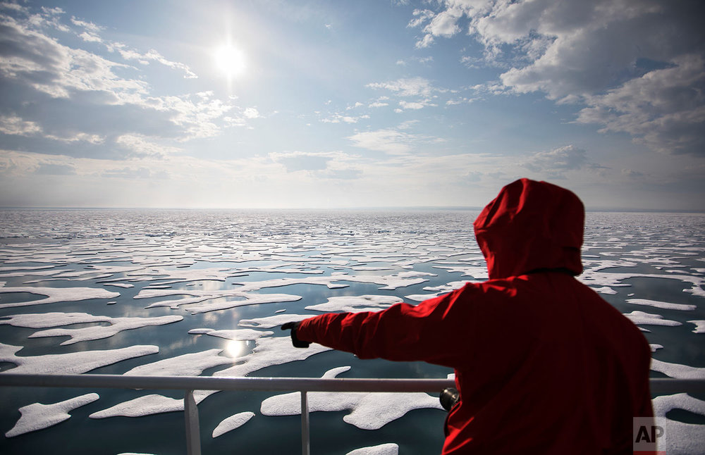 Researcher Tiina Jaaskelainen points out a possible sighting of wildlife aboard the Finnish icebreaker MSV Nordica as it traverses the Northwest Passage through the Canadian Arctic Archipelago, Saturday, July 22, 2017. As the icebreaker entered Victoria Strait, deep inside the Northwest Passage, those onboard looked for a shadow moving in the distance or a flash of pale yellow in the expanse of white that would signal the presence of the world's largest land predator. (AP Photo/David Goldman)