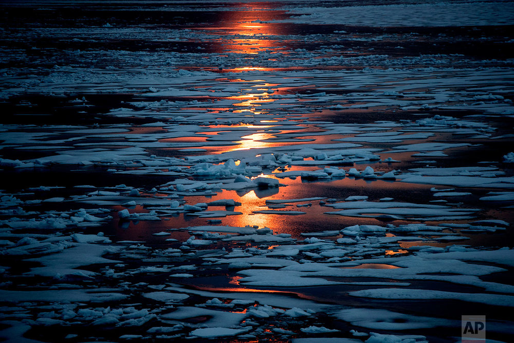 The midnight sun shines across sea ice along the Northwest Passage in the Canadian Arctic Archipelago, Sunday, July 23, 2017. The melting ice is one reason why modern ships have an easier time going through the Northwest Passage, 111 years after Norwegian adventurer Roald Amundsen achieved the first transit. Early explorers found themselves blinded by harsh sunlight reflecting off a desert of white, confused by mirages that give the illusion of giant ice cliffs all around, and thrown off course by the proximity of the North Pole distorting their compass readings. (AP Photo/David Goldman)