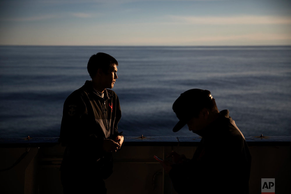 """Trainee David Kullualik, left, and Maatiusi Manning, both part of Canada's indigenous Inuit community, stand on the deck of the MSV Nordica as it traverses the Northwest Passage through Lancaster Sound in the Canadian Arctic Archipelago, Friday, July 28, 2017. Kullualik has spent time with his family hunting on the islands in the area where his grandparents grew up. """"I was imagining how my grandpa used to live, what they used to go through"""" Kullualik said of the remote lands the boat past through. """"I felt a connection all the way through."""" (AP Photo/David Goldman)"""