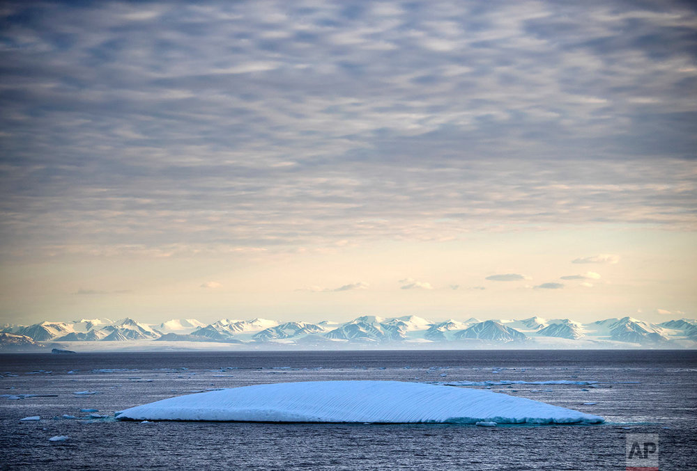 An iceberg floats past Bylot Island in the Canadian Arctic Archipelago, Monday July. 24, 2017. If parts of the planet are becoming like a furnace because of global warming, then the Arctic is best described as the world's air-conditioning unit. The frozen north plays a crucial role in cooling the rest of the planet while reflecting some of the sun's heat back into space. (AP Photo/David Goldman)