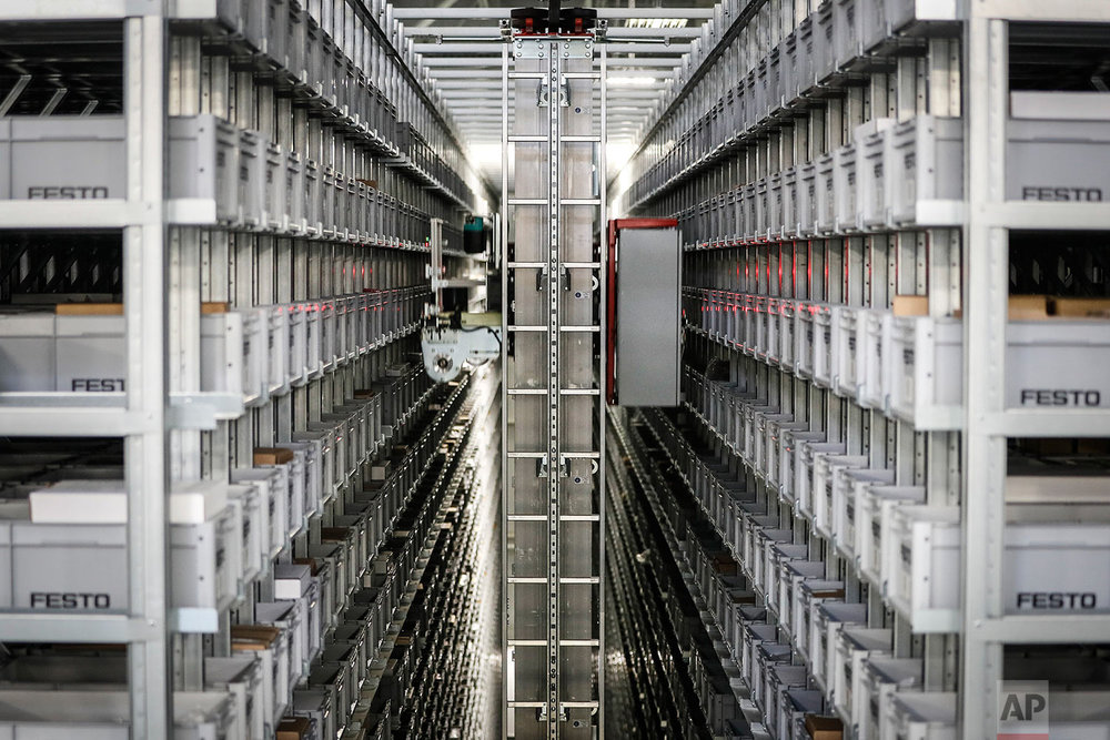"In this Wednesday, May 17, 2017 photo, a robotic conveyor uses laser guides to sort through materials storage at Festo's distribution facility in Mason, Ohio. ""This kind of factory has nothing to do with the factory we knew in the 1960s or 1980 or even 2000,"" said Yannick Schilly, vice president for North American business for Germany-based Festo, a global industrial automation company. Floors clean and aisles uncluttered, the plant is mostly quiet as workers monitor a robotic distribution system that self-adjusts its work flow to prevent backups. (AP Photo/John Minchillo)"