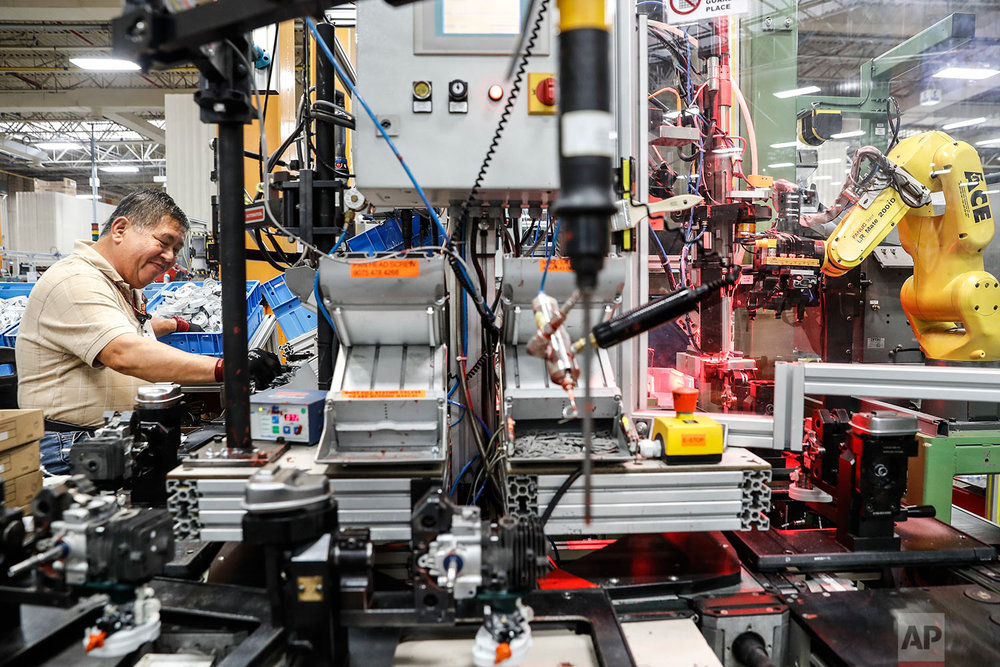 In this Thursday, May 25, 2017 photo, an assembly line laborer works across from a collaborative robot, right, at the Stihl Inc. manufacturing facility in Virginia Beach, Va. At the plant human workers are interspersed with computers and robotics that require trained technicians to service and maintain while reducing the company's need for pursuing traditional manual laborers. (AP Photo/John Minchillo)