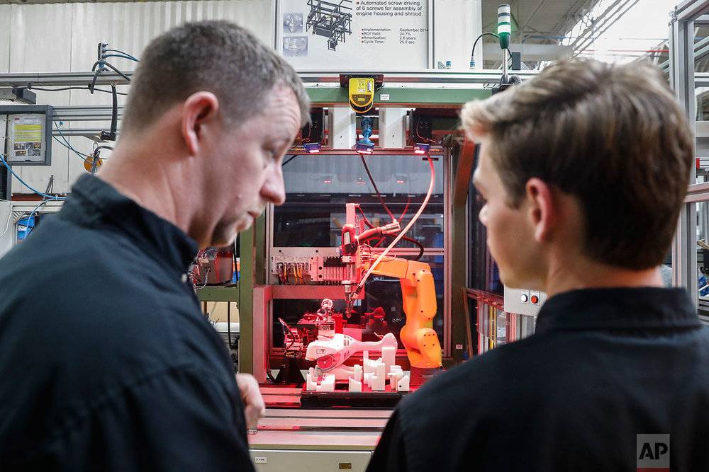 "In this Thursday, May 25, 2017 photo, A.J. Scherman, 37, left, works with fellow apprentice Ryan Buzzy, 18, right, on a robotics control computer at a chainsaw assembly line at a Stihl Inc. production plant in Virginia Beach, Va. Scherman, with only a high-school degree, wanted to earn more money when his daughter was born and took a chance with a mid-life career change. Scherman is earning a college degree as part of a Stihl apprenticeship and will finish debt-free thanks to financial aid provided by the company. ""We're safe, because we're the guys who fix the robots when they malfunction,"" Sherman said. ""We're going to need people to fix the more advanced systems. This program trains us."" (AP Photo/John Minchillo)"