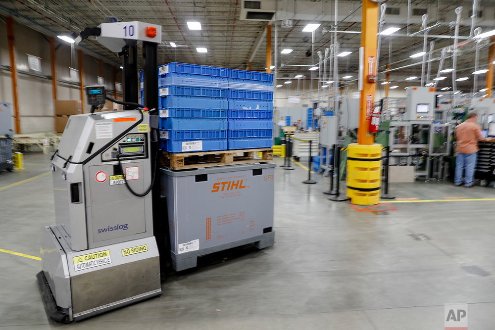 In this Thursday, May 25, 2017 photo, a robotic forklift autonomously transports materials throughout a Stihl Inc. production plant in Virginia Beach, Va. The self-driving forklifts deploy flashing lights and constant beeping sounds to navigate around corners, through doors, and operate safely around their potentially unpredictable human counterparts. (AP Photo/John Minchillo)