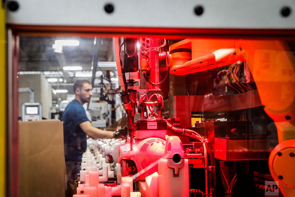 In this Thursday, May 25, 2017 photo, an assembly line laborer works alongside a collaborative robot, left, on a chainsaw production line at the Stihl Inc. production plant in Virginia Beach, Va. Despite efficiency increases and lessening the need for manual laborers, companies require workers who can program, oversee, operate, and maintain the automation. A report by Deloitte Consulting and the American Manufacturing Institute estimates 2 million such jobs will need to be filled over the next decade. (AP Photo/John Minchillo)