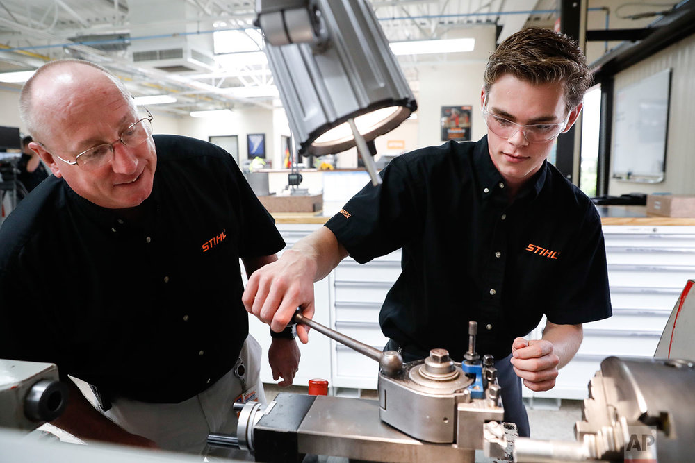 "In this May 25, 2017 photo, apprentice Ryan Buzzy, 18, right, works with Skip Johnson, left, a trainer for the Stihl Inc. apprenticeship program, on a metalworking lathe in their training area at the Stihl Inc. manufacturing facility in Virginia Beach, Va. Buzzy is being trained as a ""mechatronics technician"" at Stihl, which makes chain saws, leaf blowers and weed trimmers at its factory in Virginia. Mechatronics combines electrical and mechanical engineering, as well as computer skills. After completing Stihl's four-year apprenticeship program, he will read diagnostic software on computer screens attached to robots for repair and maintenance. (AP Photo/John Minchillo)"