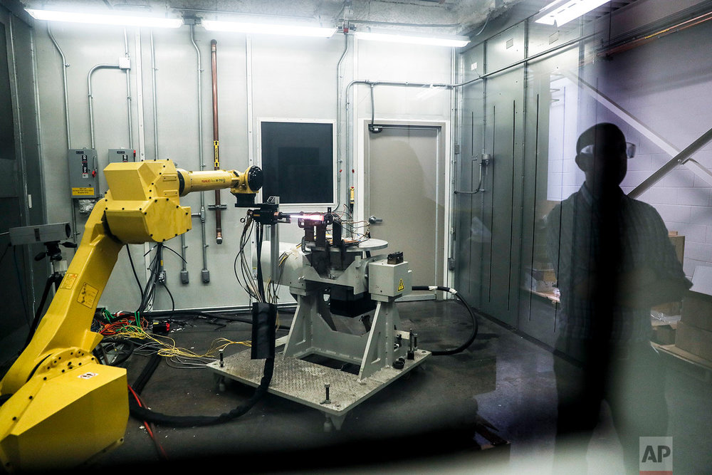 In this Thursday, May 18, 2017 photo, a robotic arm with a high-intensity blowtorch is remotely operated to test ceramic matrix composites, which make engines more durable, heat-resistant and efficient, at the General Electric Aviation plant in Evendale, Ohio. At GE Aviation, internships and co-ops with colleges attract younger prospective employees, while veteran workers are retrained. The giant Building 700 is home to white-coated scientists clustered in the FastWorks Lab nestled inside the decades old building, while much of the rest is relatively quiet. (AP Photo/John Minchillo)