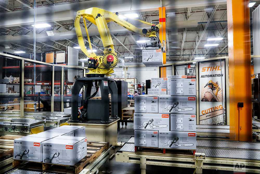 In this Thursday, May 25, 2017 photo, a giant robotic arm loads pallets full of chainsaws prepared for shipping at the Stihl Inc. production plant in Virginia Beach, Va. Despite efficiency increases and lessening the need for manual laborers, companies require workers who can program, oversee, operate, and maintain the automation. A report by Deloitte Consulting and the American Manufacturing Institute estimates 2 million such jobs will need to be filled over the next decade. (AP Photo/John Minchillo)