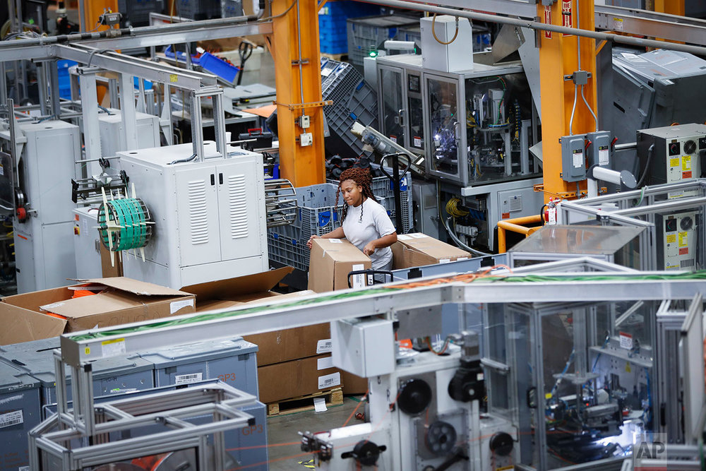 In this May 25, 2017 photo, an employee works on a factory floor at a Stihl Inc. production plant in Virginia Beach, Va. There are assembly lines at the Stihl plant, but human workers are interspersed with computers and robotics. (AP Photo/John Minchillo)