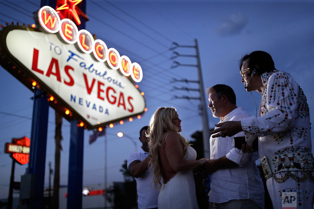 In this Aug. 1, 2017, photo, Eddie Powers, right, performs as Elvis during a wedding for Wil and Sarah Wilson in Las Vegas. Powers works full-time as an Elvis tribute artist performing at weddings and leading Elvis themed tours around Las Vegas. (AP Photo/John Locher)