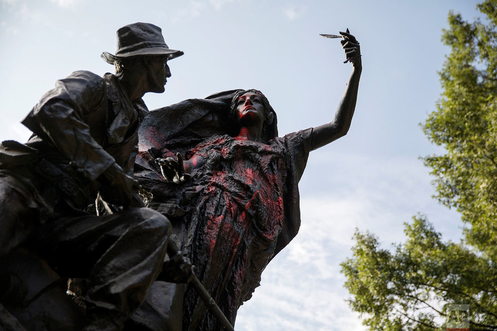 A statue depicting a Confederate soldier in Piedmont Park in Atlanta is vandalized with spray paint Monday, Aug. 14, 2017, from protesters who marched through the city last night to protest the weekend violence in Charlottesville, Virginia. (AP Photo/David Goldman)