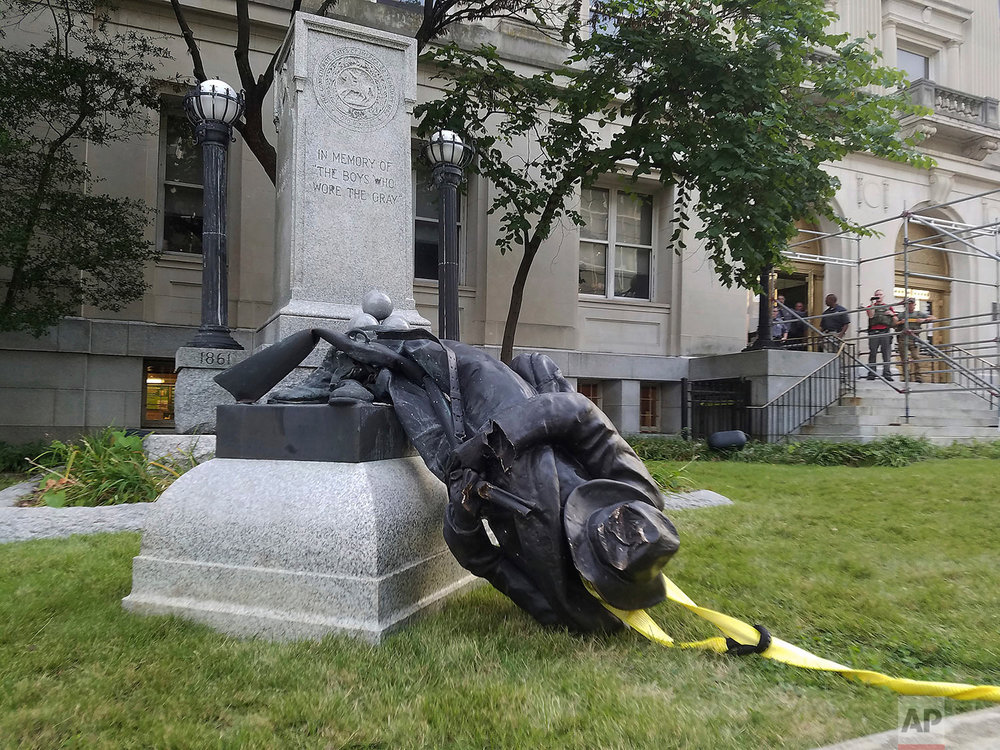 A toppled Confederate statue lies on the ground on Monday, Aug. 14, 2017, in Durham, N.C. Activists on Monday evening used a rope to pull down the monument outside a Durham courthouse. The Durham protest was in response to a white nationalist rally held in Charlottesville, Va, over the weekend. (Virginia Bridges/The Herald-Sun via AP)