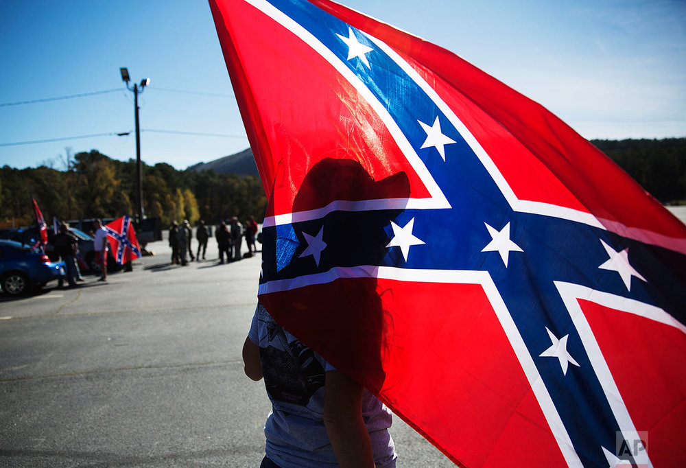 Tara Brandau, of Lake City, Fla., casts a shadow against a confederate flag as supporters gather before hiking up Stone Mountain during a rally Saturday, Nov. 14, 2015, in Stone Mountain, Ga. The rally was organized in response to a proposal to place a monument dedicated to Martin Luther King Jr. at the top of the mountain. (AP Photo/David Goldman)