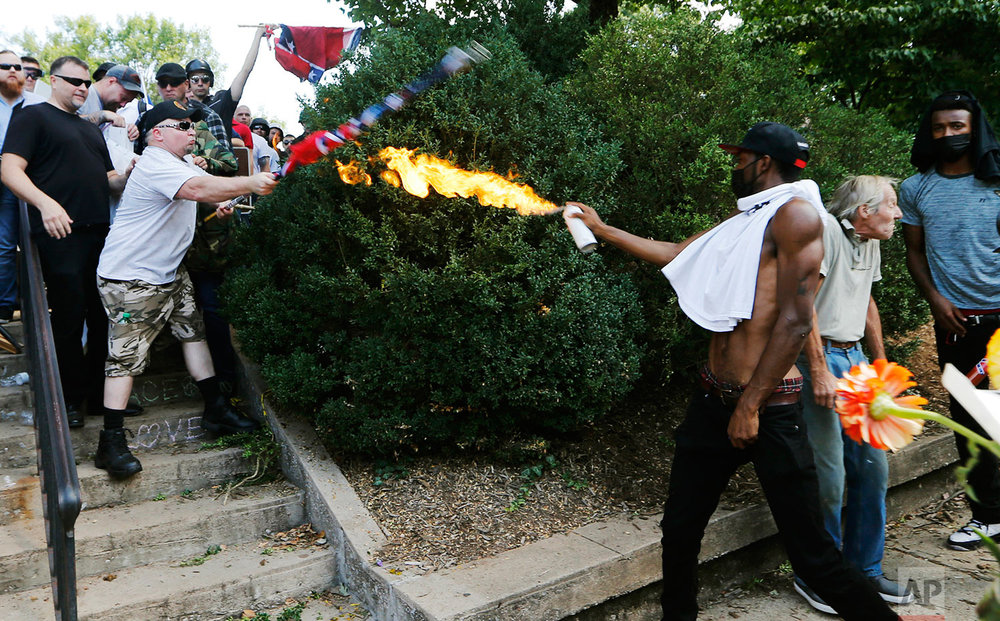 A counter demonstrator uses a lighted spray can against a white nationalist demonstrator at the entrance to Lee Park in Charlottesville, Va., Saturday, Aug. 12, 2017. (AP Photo/Steve Helber)