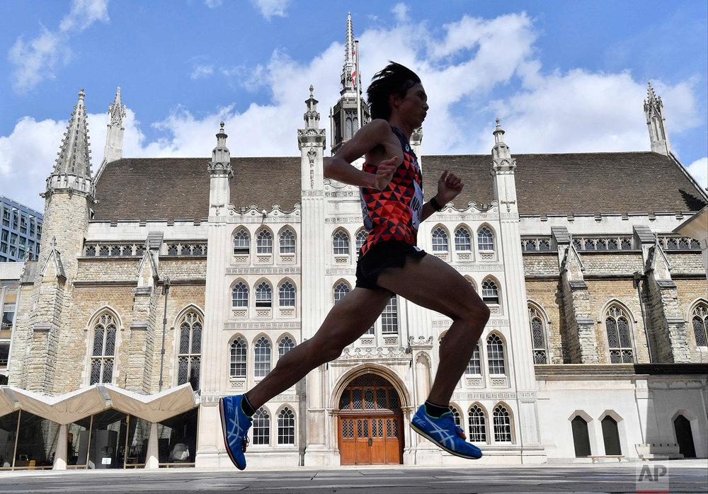 Japan's Kentaro Nakamoto runs past the Guildhall in the Men's Marathon during the World Athletics Championships Sunday, Aug. 6, 2017. (AP Photo/Martin Meissner)