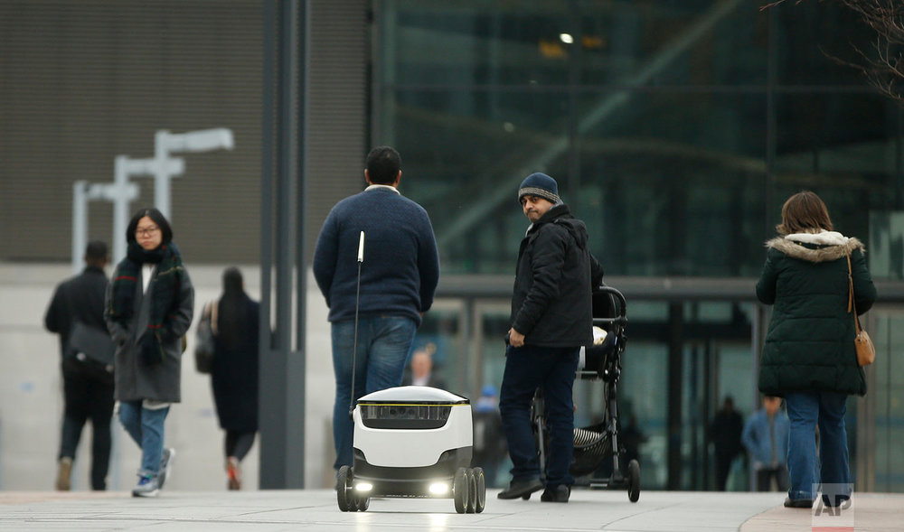 In this Thursday, March, 10, 2016 photo, a pedestrian looks back at a delivery robotic device that has the capacity to hold 6-8 kilograms (13-17 pounds) of cargo in London. The six wheeled intelligent robot that uses GPS systems will make its debut in Greenwich after talks with the local authority led to a partnership with the firm. Greenwich is one of the few areas in the UK that allows unmanned robotic units to be used in public under special license. (AP Photo/Alastair Grant)