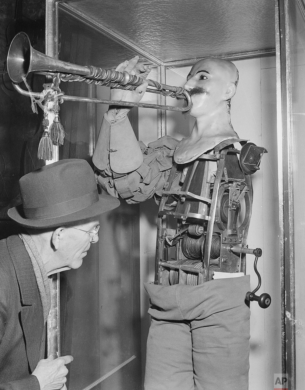 "In this April 30, 1950 file photo, a man inspects what is said to be the first robot in history on display in the Deutsches Museum in Munich. The ""soldier,"" which has an automatic bellows that blows a trumpet, was made in 1810 by Friedrich Kauffman of Dresden, Germany (AP Photo/Heinrich Sanden)"