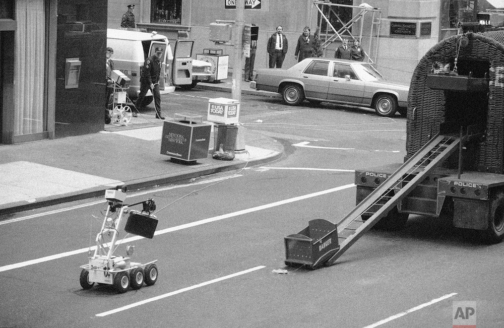 In this Wednesday, April 20, 1983 file photo, a bomb removal robot, remote controlled by police, at left around the corner, carries a briefcase believed to be a bomb to a waiting truck in New York. It turned out that the suitcase held telephone repairman tools. (AP Photo/David Bookstaver)