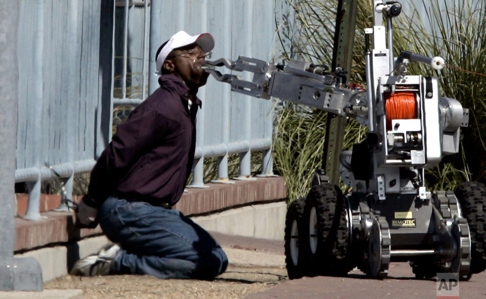 In this Monday, Oct. 3, 2005 photo, a man is disarmed by a robot outside a Wells Fargo bank he tried to rob in Tucson, Ariz. Police said Sgt. Jeffry Leon Lewis Jr., 33, an Army sergeant from Fort Huachuca, walked into the bank branch here Monday and presented a note saying he had a bomb in his mouth, which was covered in duct tape. No explosives were found in his mouth or backpack or in his vehicle parked nearby, according to police. (Benjie Sanders/Arizona Daily Star via AP)