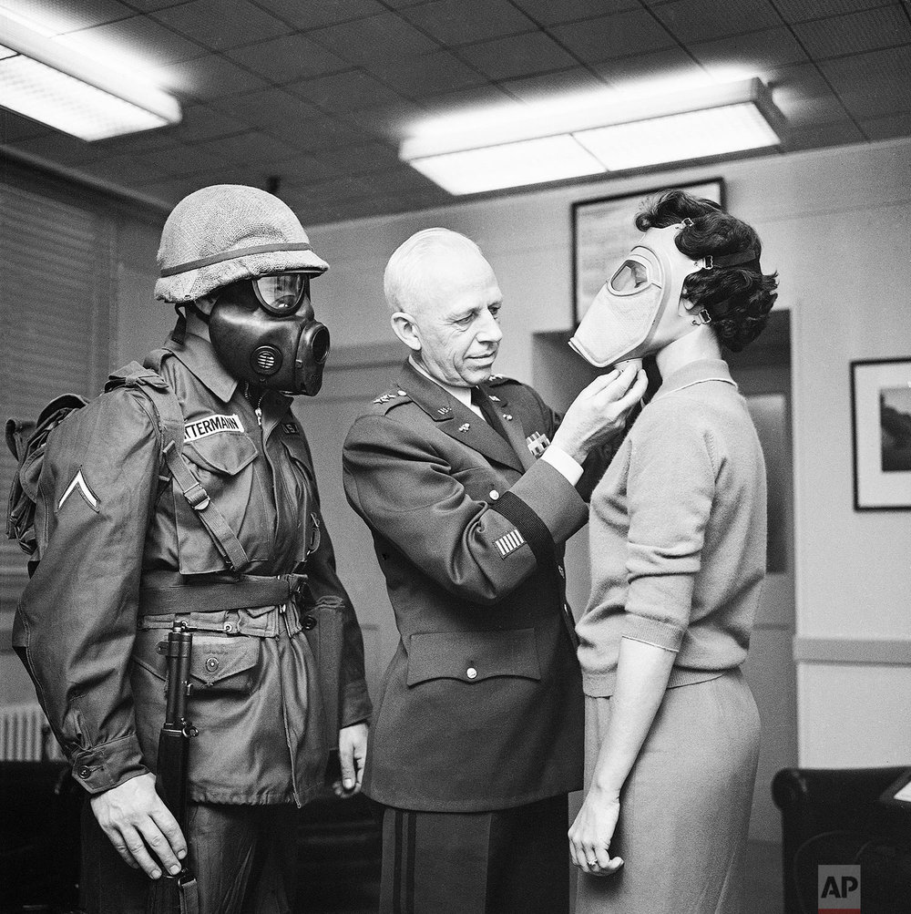 In this Jan. 19, 1959 photo, Pfc. Warner Bitterman, left, watches as Army chief chemical officer Maj. Gen. Marshall Stubbs, center, checks new civilian gas mask being worn secretary Margaret Francis at his Pentagon office in Washington. (AP Photo)