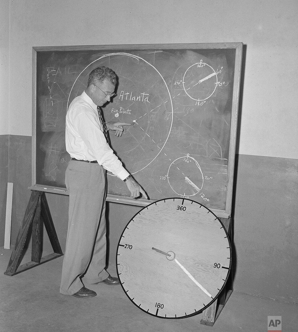 "Civil Defense director George M. Phillips of the Atlanta, Ga., area, illustrates he use of a ""flash dial"", a simple wooden disc, 36 inches in diameter, created to spot the heart of any atomic explosion within a matter of minutes, in Atlanta, June 16, 1951. The disc has a center pole which casts a ""shadow"" when heat waves from an atomic blast sear the surface of the wood. (AP Photo/Horace Cort)"