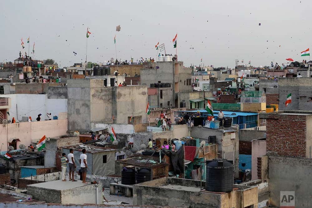 In this Tuesday, Aug. 15, 2017 photo, Indians fly kites on rooftops during Independence Day celebrations in the old quarters of New Delhi, India. (AP Photo/Tsering Topgyal)