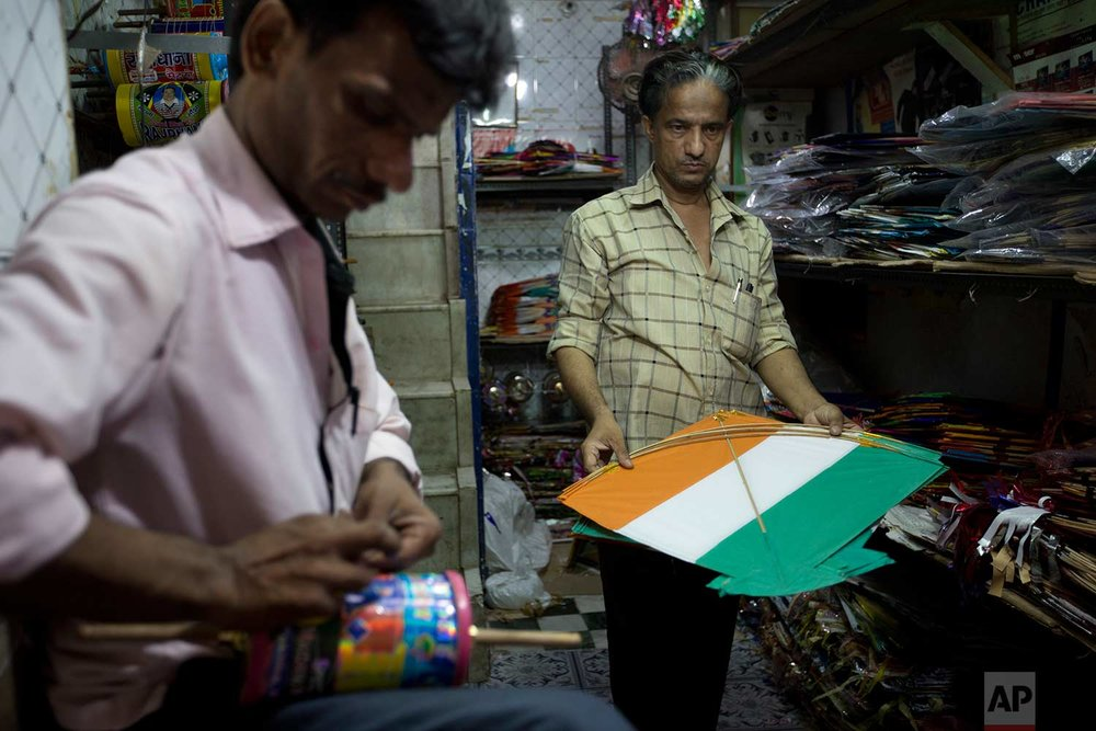 In this Tuesday, Aug. 15, 2017 photo, a kite seller holds a kite to hand over to a customer on Independence Day in the old quarters of New Delhi, India. (AP Photo/Tsering Topgyal)