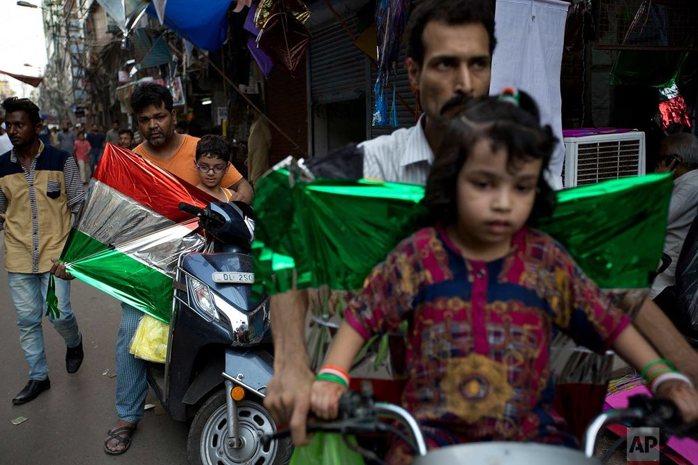 In this Tuesday, Aug. 15, 2017 photo, Indians ride motorbikes carrying kites to fly on Independence Day in the old quarters of New Delhi, India. (AP Photo/Tsering Topgyal)