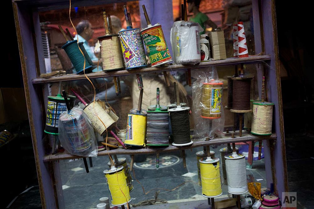 Rolls of kite strings are displayed for sale in the old quarters of New Delhi, India, Thursday, Aug. 17, 2017. (AP Photo/Tsering Topgyal)