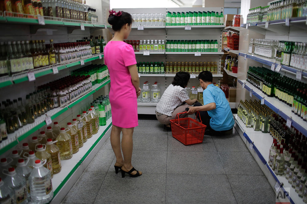In this Monday, June 19, 2017, photo, a Potonggang department store staff member waits to assist a couple shopping for local alcohol in Pyongyang, North Korea. (AP Photo/Wong Maye-E)