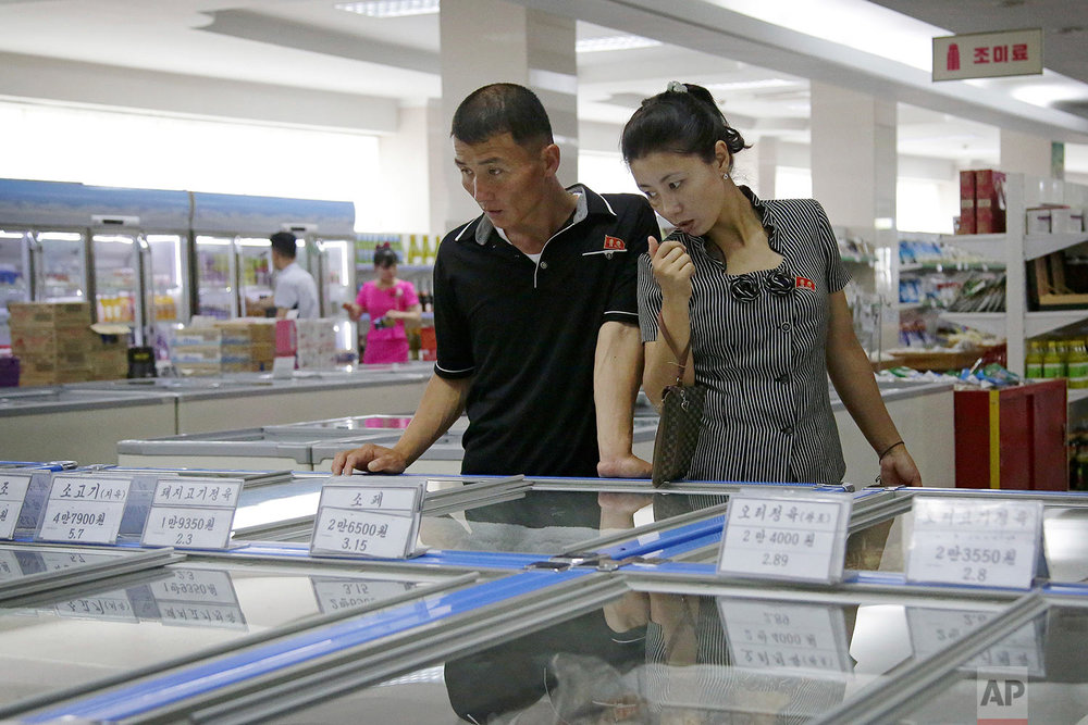 In this Monday, June 19, 2017, photo, a couple browse through the frozen foods section at the Potonggang department store in Pyongyang, North Korea. (AP Photo/Wong Maye-E)