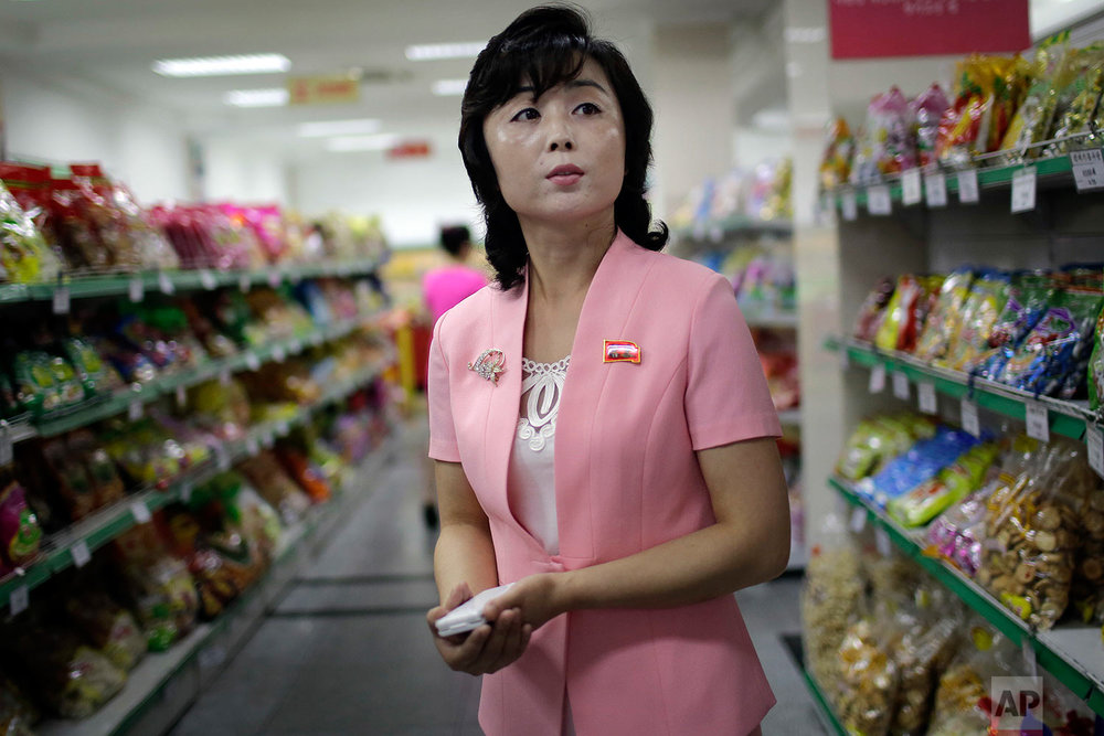 In this Monday, June 19, 2017, photo, Song Un Pyol, manager at the Potonggang department store stands in the snacks aisle while being interviewed by The Associated Press in Pyongyang, North Korea. (AP Photo/Wong Maye-E)