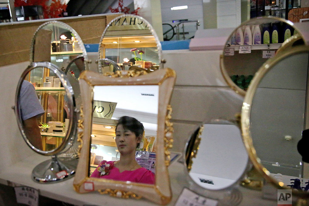 In this Monday, June 19, 2017, photo, a staff member is seen reflected in a mirror for sale at the Potonggang department store in Pyongyang, North Korea. (AP Photo/Wong Maye-E)
