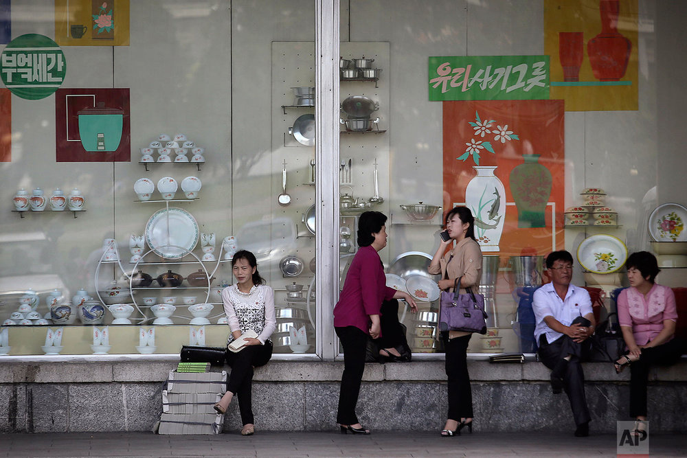 In this Saturday, June 25, 2016, photo, people sit in front of a window display of household items at a department store in Pyongyang, North Korea. (AP Photo/Wong Maye-E)