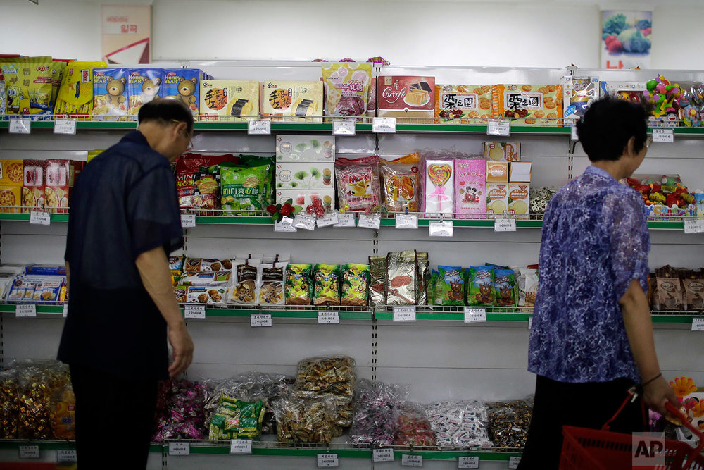 In this Monday, June 19, 2017, photo, people walk past a shelf displaying both local and imported snacks from China at the Potonggang department store in Pyongyang, North Korea. (AP Photo/Wong Maye-E)