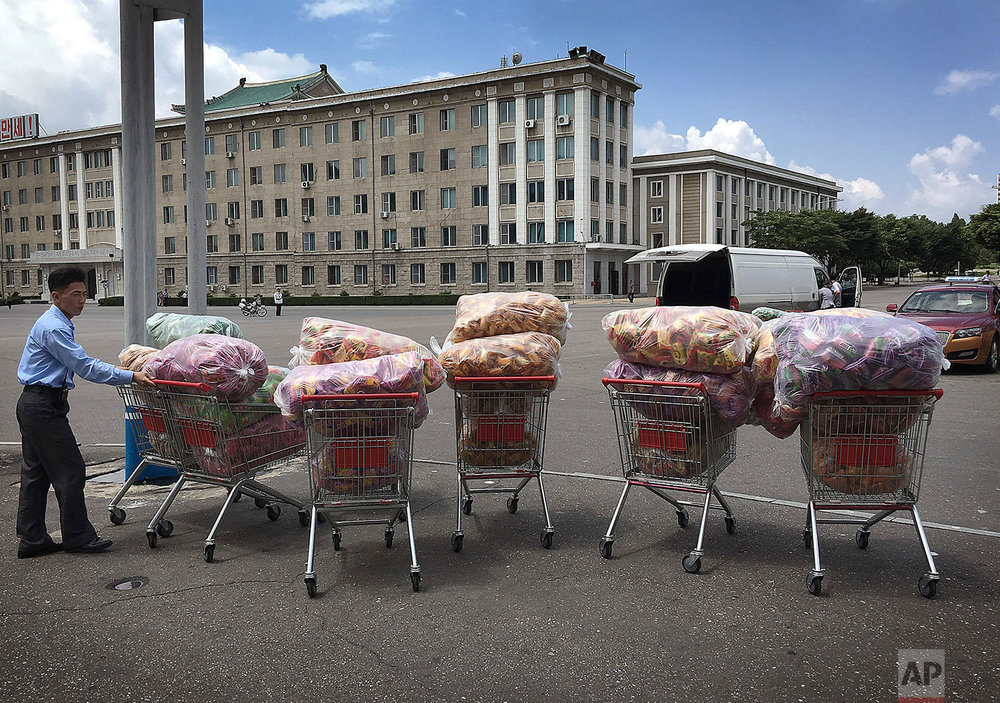In this Saturday, June 25, 2016, photo, a man waits with shopping carts at a parking lot in front of a department store in Pyongyang, North Korea.  (AP Photo/Wong Maye-E)
