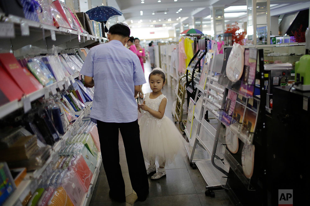 In this Monday, June 19, 2017, photo, a young girl and her father shop in the stationery department at the Potonggang department store in Pyongyang, North Korea. (AP Photo/Wong Maye-E)