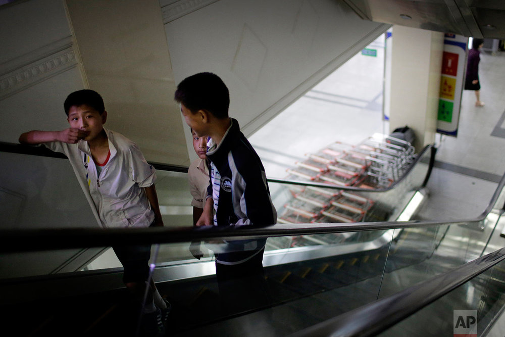 In this Monday, June 19, 2017, photo, boys ride an escalator which takes them to the household items and stationery section of the Potonggang department store in Pyongyang, North Korea. (AP Photo/Wong Maye-E)