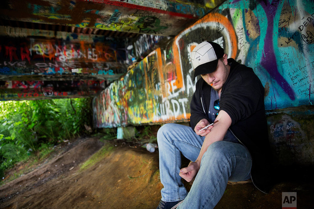 Forrest Wood, 24, injects heroin into this arm under a bridge along the Wishkah River at Kurt Cobain Memorial Park in Aberdeen, Wash., Tuesday, June 13, 2017. Wood grew up here, watching drugs take hold of his relatives, and he swore to himself that he would get out of this place, maybe spend his days in the woods as a park ranger. But he started taking opioid painkillers as a teenager, and before he knew it he was shooting heroin, a familiar first chapter in the story of American addiction. (AP Photo/David Goldman)