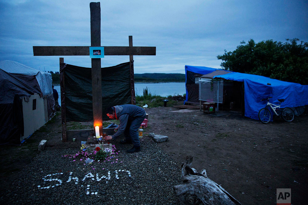 A mourner lights a candle at the memorial marking the spot where Shawn Vann Schreck died two days before in a homeless encampment where he lived along the river in Aberdeen, Wash., Wednesday June 14, 2017. On Aberdeen's banks, residents of the homeless encampment pulled driftwood from the water to construct a cross, 8 feet tall, to honor their latest loss: Vann Schreck, 42, who died slowly from heart and lung ailments made worse by infrequent medical care and longtime addiction. A generation ago, people like him went to work in the mills and bought tidy houses in nice neighborhoods, says the Rev. Sarah Monroe, a street minister here. (AP Photo/David Goldman)