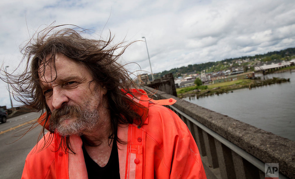 "Aberdeen, Wash., stands in the background as Pete Rasmussen, 58, walks over a bridge to return home Friday, June 16, 2017. The former logger who has been out of work for over a year needs hip surgery and worries a new Washington healthcare law could strip his benefits. ""I want to get it done before they do anymore changes,"" said Rasmussen. (AP Photo/David Goldman)"