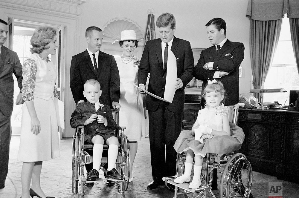 President John Kennedy looks at  a gift from Bobbie Whittaker, 7,  in his White House office in Washington, June 20, 1963.  Bobbie and his six-year-old sister, Kerrie, right, are the new national poster children of the Muscular Dystrophy Association. Standing, from left, are actress Patty Duke; the children's parents, Mr. and Mrs. C. Leigh Whittaker of Cincinnati; Kennedy and comedian Jerry Lewis.  Kennedy received a lapel pin from Bobby, flowers from Kerrie.    (AP Photo/John Rous)