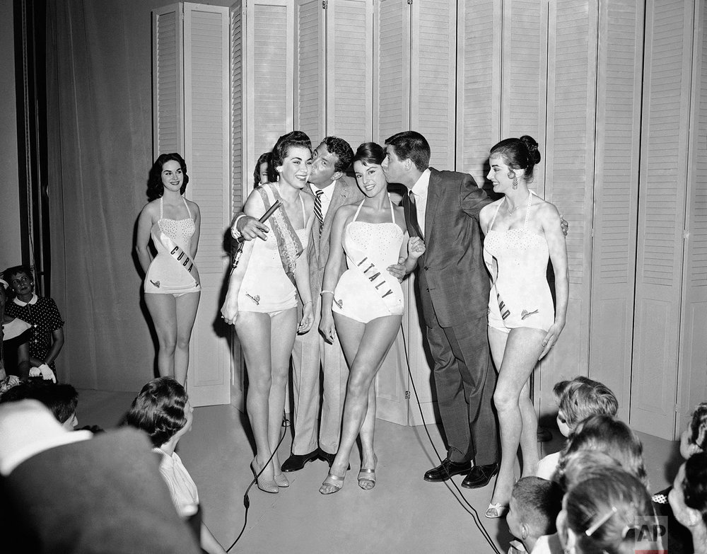 The comedy team of Dean Martin, left center, and Jerry Lewis, right center, often rumored to be separating, get together with these foreign beauties during a swimsuit fashion show in a department store, July 9, 1956, New York. From left are: Maria Cordoso, Miss Brazil; Martin; Rosanna Galli, Miss Italy; Lewis; and Iris Waller, Miss England. The girls will compete for Miss Universe in the international beauty contest in Long Beach, Calif., starting on July 12. (AP Photo/John Lindsay)