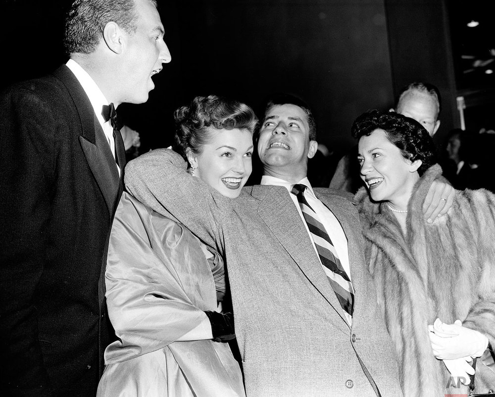 "Actor-comedian Jerry Lewis, center, with his wife, singer Patti, right, pretends to wrestle-hold actress Esther Williams as her husband, radio announcer Ben Gage, reacts at a benefit premiere of ""Father's Little Dividend"" in Hollywood, Ca., April 5, 1951.  (AP Photo)"